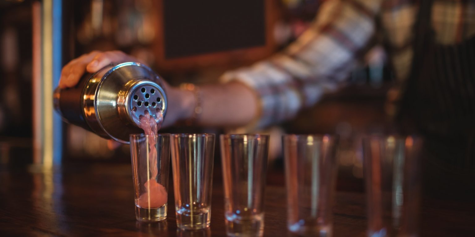 Bartender pouring cocktail drink into shot glasses at counter
