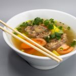image of oxtail soup in a bowl with chopsticks resting on top of the bowl