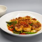 scallop with xo sauce in a dish with chopsticks