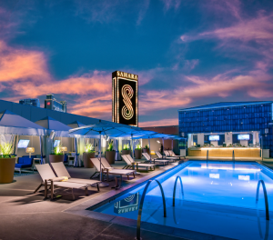 Image of the Retro Pool at dusk with daybeds and cabanas on the left hand-side and the SAHARA marquee in the distance