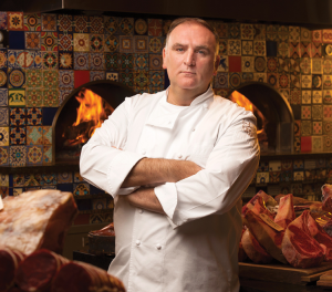 Jose Andres standing in from of flame ovens surrounded by meat