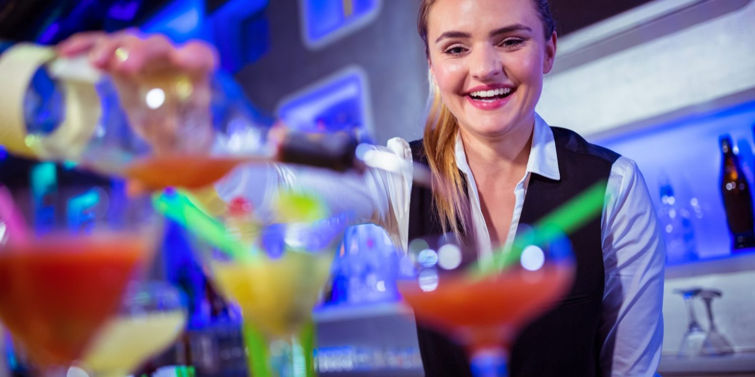 Smiling bartender pouring drink in glass