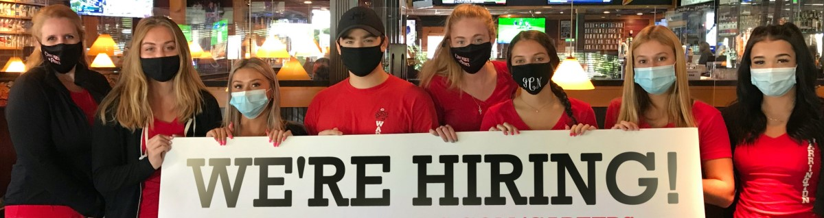 staff members with mask holding up a hiring sign
