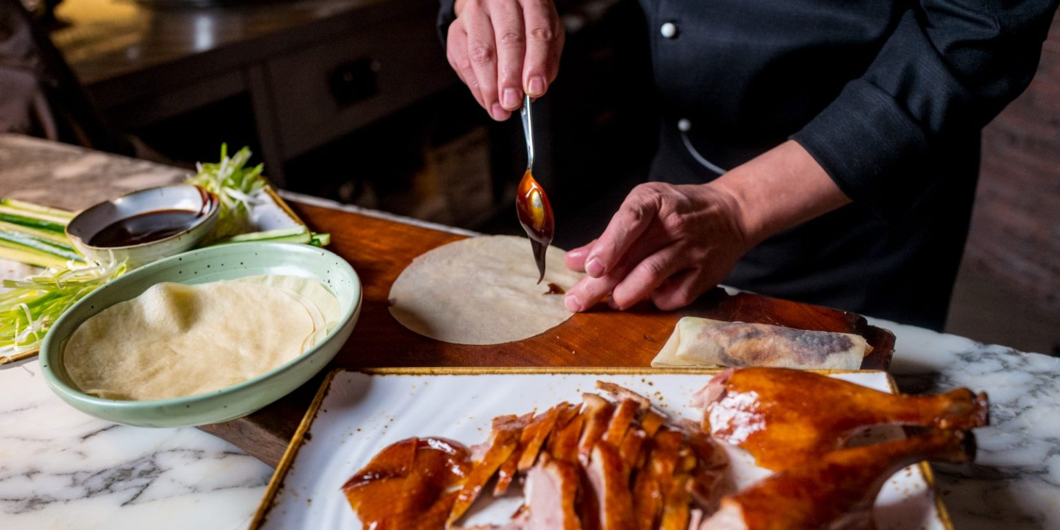 Chef pictured applying sauce to a tortilla with cooked duck in the foreground
