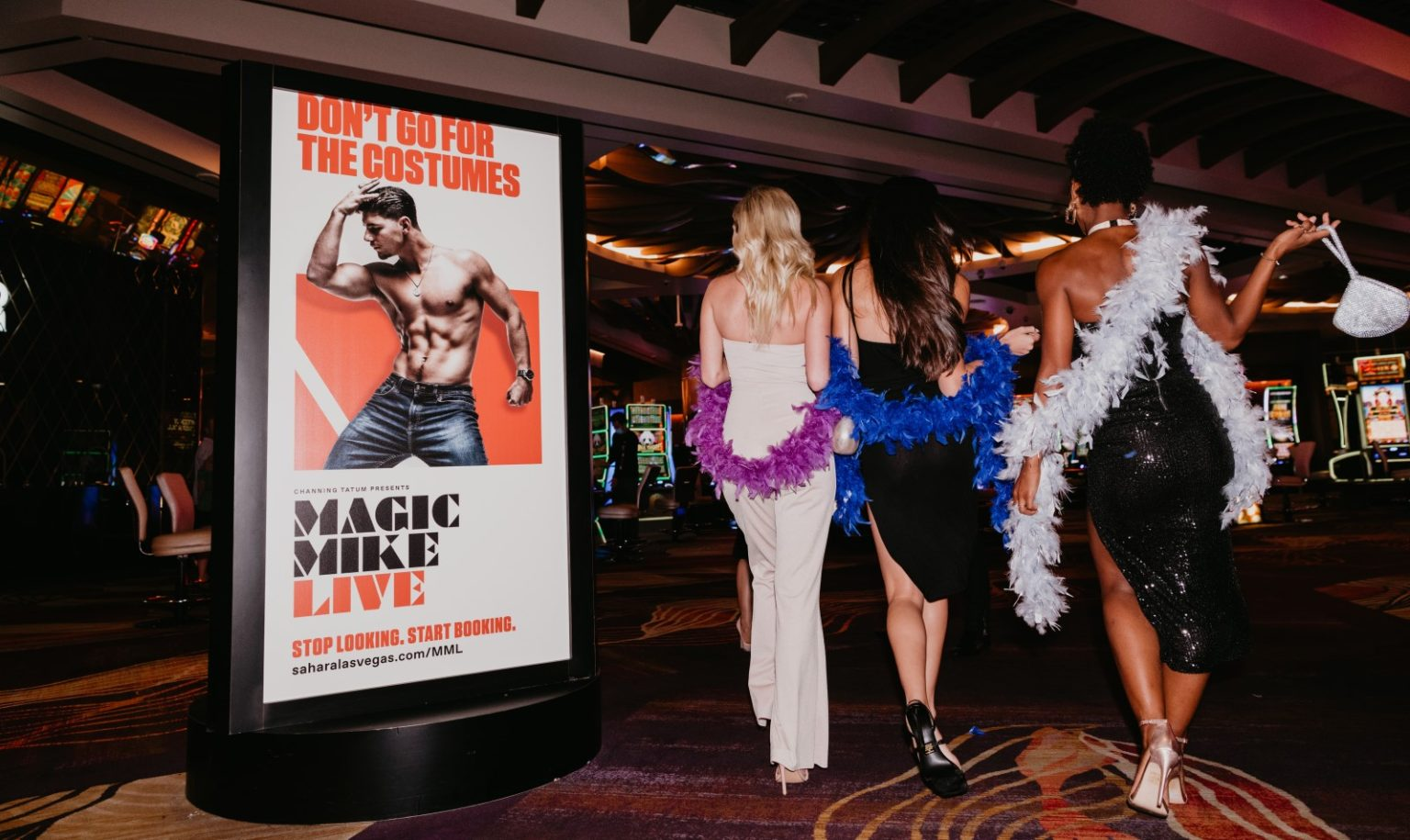 Three ladies with leis walking across the casino looking at Magic Mike Live sign